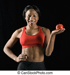 Athletic woman holding apple.