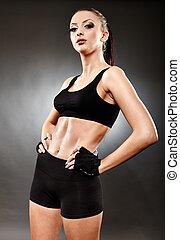 Athletic woman in sportswear standing akimbo