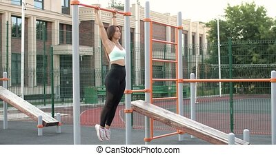 Athletic woman is hanging on horizontal bar and pulling up her legs to a chest.