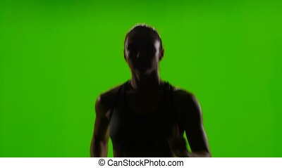 Athletic woman is jogging. Front view. Green screen