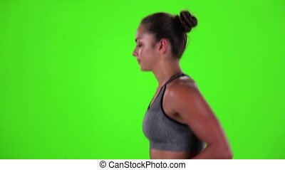 Athletic woman is jogging. Side view. Green screen. Slow motion