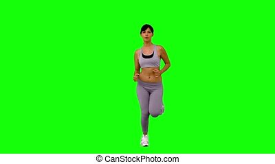 Athletic woman jogging on green screen in slow motion