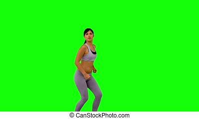 Athletic woman leaping and posing on green screen in slow...