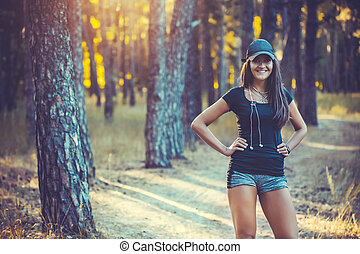 athletic woman listening music on a running in forest -...
