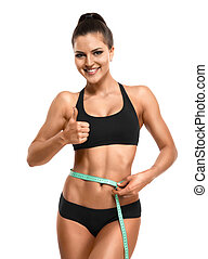 Athletic woman measuring her waist  and showing thumb up isolate