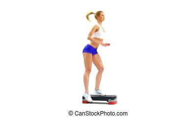 Athletic woman performing step aerobics exercise, on white...