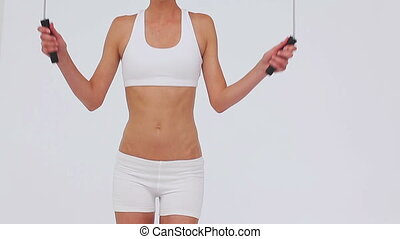 Athletic woman playing with a skipping rope