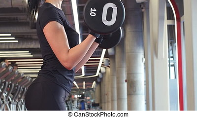 Athletic woman pumping up muscules with barbell.