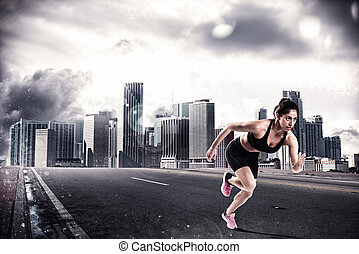 Athletic woman runner on the asphalt of a city road