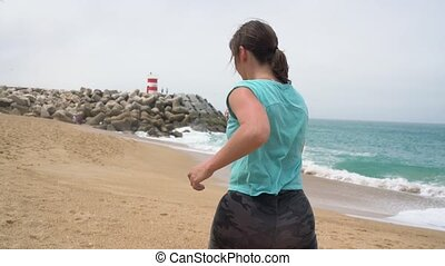Athletic woman running along the beach. Portuguese coast of...