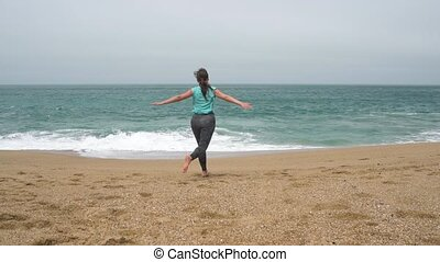 Athletic woman running along the beach. Slow motion
