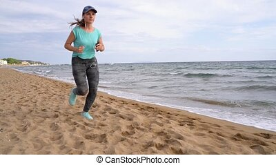 Athletic woman running along the beach. Video at different...
