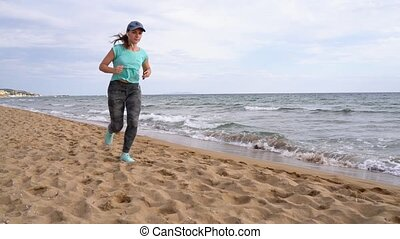 Athletic woman running along the beach. Greek coast of the...