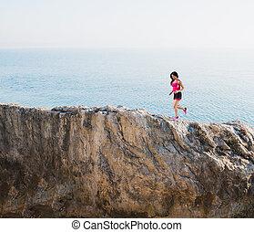 Athletic woman runs on a high mountain