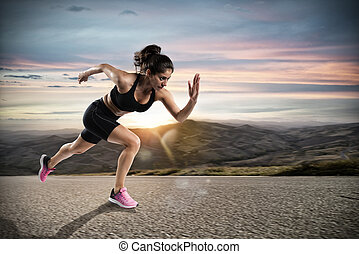 Athletic woman runs on the street during sunset