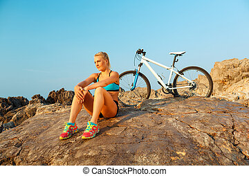 Athletic woman sitting on the rocks after a bike ride and enjoy the view