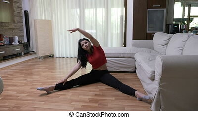 Athletic woman stretches on the floor in her living room at home