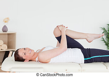 Athletic woman stretching her leg while looking at the camera