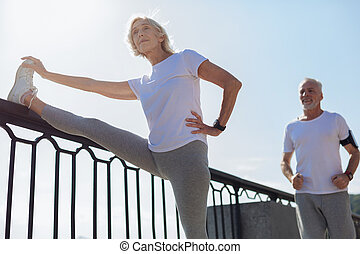 Athletic woman stretching while her husband running