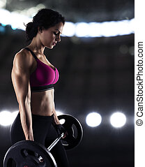 Athletic woman training biceps at the gym