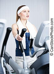 Athletic woman training on simulators in gym