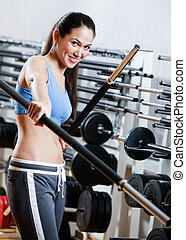 Athletic woman with dumbbells stick