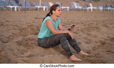 Athletic woman with headphones sits on the beach and rests...