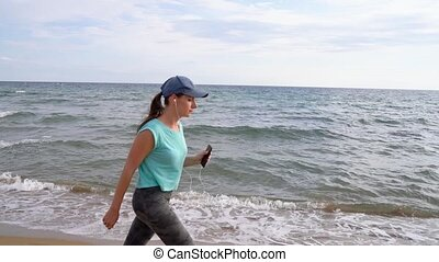 Athletic woman with headphones walking along the beach. Slow motion