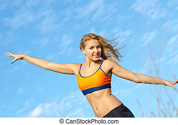 Athletic woman with a bare midriff standing against blue sky with her arms outstretched