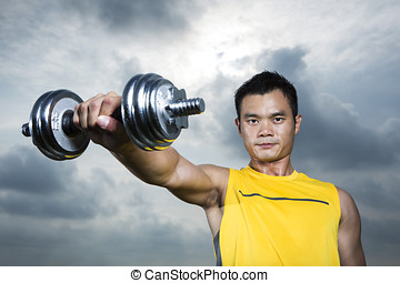 Athletic Young Chinese man exercising outdoors with ...