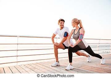 Athletic young couple doing stretching legs exercises together