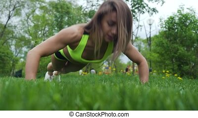 Athletic young female doing push ups