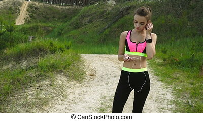 athletic young girl turk on music in headphones and running...