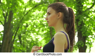 athletic young lady drinks water from a bottle