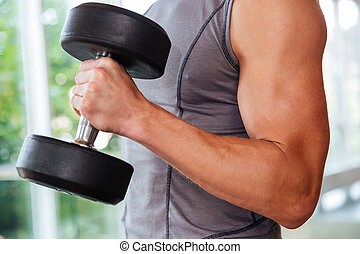 Athletic young man athlete training using dumbbells in gym