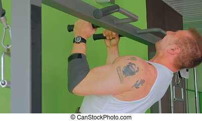 Athletic young man doing chin-ups at gym, fitness club....
