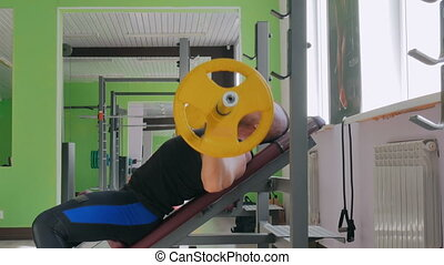 Athletic young man doing exercises with barbell at gym, fitness club