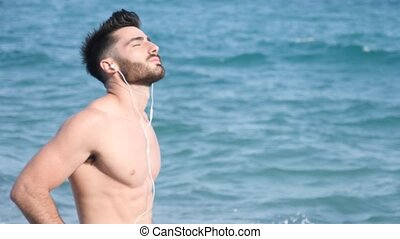 Athletic young man on beach listening to music