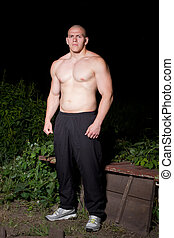 Athletic young man outdoors at night