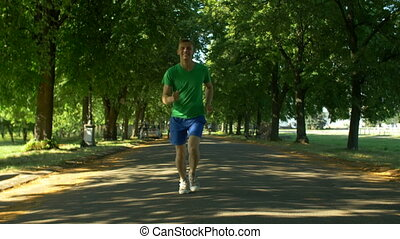 Athletic young man running in public park