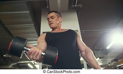 Athletic young man training his bicep with dumbbells in a gym