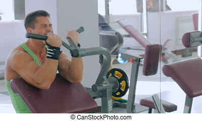 Athletic young man working out on fitness exercise equipment at gym