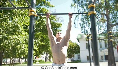 Athletic young muscular man pulled-up on horizontal bar in summer park