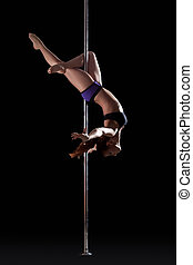 Athletic young pole dancer, isolated on black
