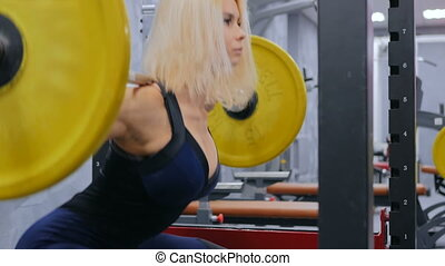 Athletic young woman doing exercises with barbell at the gym