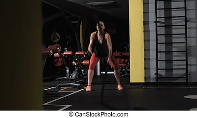 Athletic young woman doing some crossfit exercises with a rope