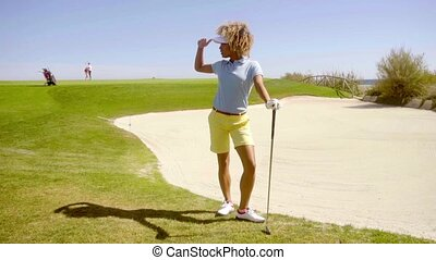 Athletic young woman golfer standing leaning on her club at...