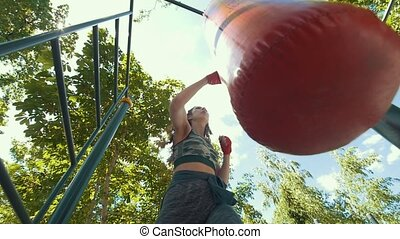 Athletic young woman in sportswear beats a punching bag,...
