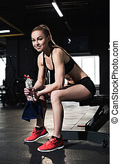 Athletic young woman in sportswear holding towel and bottle of water in gym