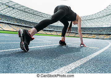 Athletic young woman in sportswear in starting position on running track stadium